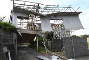 台風24号で損壊した建物の復旧作業を行う業者=6日、伊仙町目手久