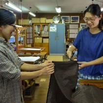 完成した大島紬にはさみを入れる支援者(右)と森さん=25日、奄美市名瀬