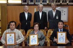 奄美市一集落1ブランド認定を受けた3町内会の代表ら=30日、市役所
