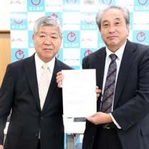 地域産業資源活用事業認定書の交付を受けた㈱ヘルシーアイランズの藤山社長(写真左)=17日、徳之島町役場