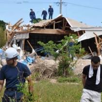 爆発事故の現場を調査する陸上自衛隊の不発弾処理隊員や警察、消防署員ら=26日、喜界町湾