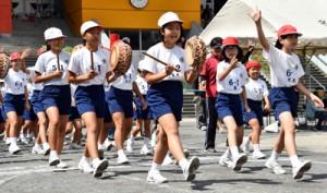 ヨコ長八月踊りの「ムチムレ」を歌いながら入場する児童たち=1日、奄美市の名瀬小学校