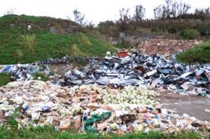 ②一般ごみやトタンなどの災害ごみが山積みとなっている粗大ごみ置き場=12日、喜界町湾
