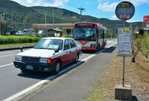 龍郷町内で運行を開始したタクシー車両=2日、同町中勝のバス停「ビッグⅡ前」