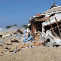 爆風で壊れた倉庫と土砂が吹き飛ばされ穴が開いた現場=18日午後2時15分ごろ、喜界町湾