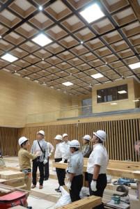 内装工事が進む議場を見学する市議ら。天井は紬の幾何学模様をイメージしたデザイン=13日、奄美市名瀬の市本庁舎建設工事現場