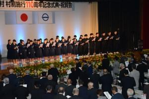 大和村制施行110周年記念式典で村民歌を斉唱する出席者=25日、大和村思勝