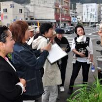 中心商店街を歩き、身近にある観光資源を再確認する参加者=17日、奄美市名瀬