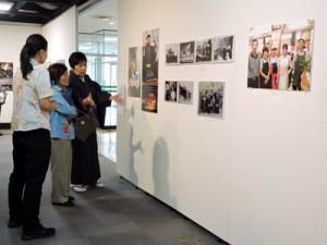 大島紬姿で来場者を迎える松村久美さん(上の右端)。生い立ちを語る大里さんと在留許可証明書の写真=27日、那覇市民ギャラリー