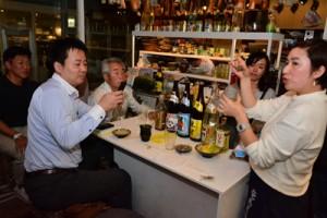 黒糖焼酎の飲み方や奄美の食材を使ったつまみなどを提案した石原さん(右)=24日、東京・吉祥寺