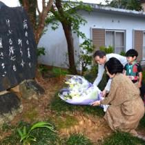 文学碑に献花する(左から)島尾伸三さんと潤井理事長ら=12日、奄美市名瀬
