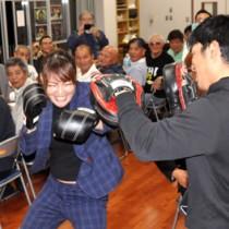 後援会主催の祝勝会でミット打ちを披露する吉田選手=13日、知名町