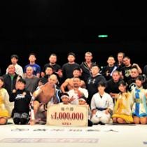 菊野さん(中央)を囲んで撮影する選手ら=11日、鹿児島市
