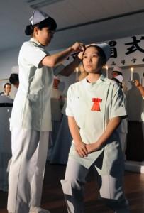 「戴帽の儀」でナースキャップを授かる生徒=7日、奄美高校