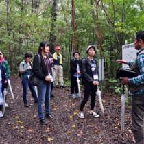 ガイドから奄美の自然環境について説明を受けるモニターツアー参加者(左)=5日、奄美市名瀬の金作原国有林