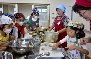 講師に教わりながらアオリイカを切る児童=17日、龍郷町りゅうがく館