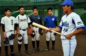 中学生にバッティングのアドバイスをする宮本内野手(右)=10日、名瀬運動公園市民球場