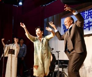 ベイスターズ歓迎パーティーで歌手の元ちとせさんと六調を踊るラミレス監督=5日、奄美市名瀬