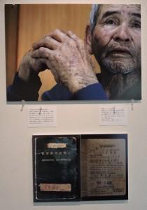 「沖縄に生きる奄美」写真展② 生い立ちを語る大里さんと在留許可証明書の写真
