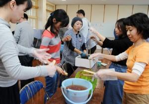 佐田さん(中央)の指導の下、イトバショウの繊維取りを体験する受講生ら=24日、瀬戸内町俵
