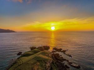 2018くになおフォトコンテストで最優秀賞を受賞した渡武志さんの「島一番の夕日とササント」(提供写真)