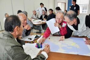 地図上に観光資源を落とし込み、ルート案について話し合う参加者=29日、龍郷町