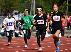 【40代女子100㍍】力走する各地区の選手たち=11日、奄美市名瀬運動公園陸上競技場
