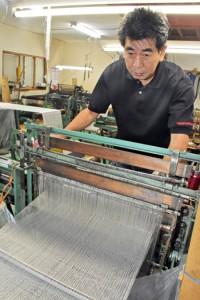 大島紬の織機に向かう正樹さん=10月11日、鹿児島市