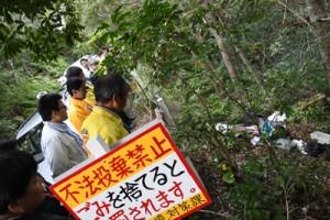 山間部に捨てられた衣類など家庭ごみを確認する参加者=21日、奄美市名瀬
