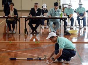 審査員の前で清掃作業を行う受検者=12日、龍郷町の県立大島養護学校体育館