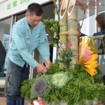門松を設置する龍郷町の施設利用者=26日、奄美市笠利町の奄美空港