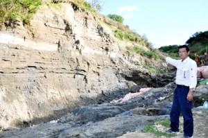 地層がむき出しとなっている「長嶺の島尻層群」を指し示す喜界町企画観光課の富課
