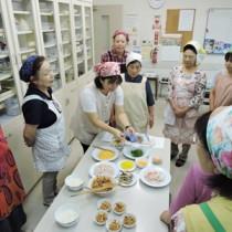 鶏飯の盛り付け方を教える奥田千草さん(左から5人目)、アシスタントの長女千恵さん(同3人目)=8日、沖縄県那覇市