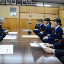 受賞を報告する朝日中吹奏楽部の(右側手前から)橋口顧問と代表生徒4人(右側)=12日、奄美市役所