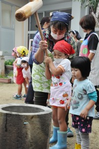 石臼ときねを使って本格的な餅つきを体験する子どもら=7日、奄美市笠利町
