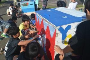 与論島の海岸からごみがなくなることを願い、拾い箱にイラストを描く茶花小の児童たち=22日、与論町の同校