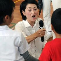 「こんにちは」と子どもたちにマイクを向ける稲田直美さん=11月17日、龍郷町