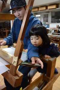 機織り体験する親子=11月22日、龍郷町大勝