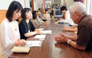 戦争体験者から聞き取り調査をする鹿児島大学の学生(左)=2日、龍郷町