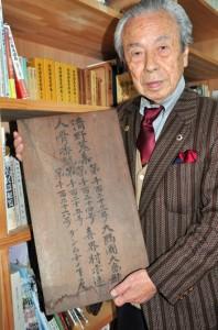 大津代表が沖縄から持ち帰った遺骨保管箱のふたとみられる板=19日、奄美市名瀬