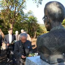 泉芳朗の胸像に献花する参加者=25日、奄美市名瀬のおがみ山公園