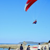 子どもたちの待つ海岸へパラグライダーで舞い降りるサンタクロース=22日、龍郷町安木屋場集落