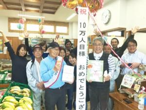「加計呂麻島のいっちゃむん市場」10万人目の来場者となった髙橋司さん(前列左)=19日、瀬戸内町(提供写真)