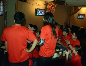 テレビで試合を見守る応援者=23日、瀬戸内町古仁屋の飲食店