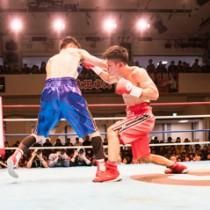 最終5R、相手の顔面にパンチを浴びせる峯田選手(右)=23日、東京。後楽園ホール