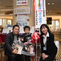150万人目の入館者となった泉玲央君(中央)と父の智憲さん(左)。右は有村館長=15日、県立奄美図書館
