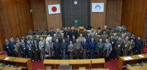 現庁舎最後の定例会を終え、大島紬姿で写真に収まる議員と執行部ら=26日、奄美市役所の議場