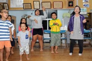 芝田美保子さん(右)に合わせ、踊りを練習する子どもたち