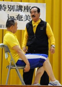 手本を示しながらトレーニング方法を指導した宮畑さん(後方)と中村トレーナー=15日、奄美市名瀬総合体育館