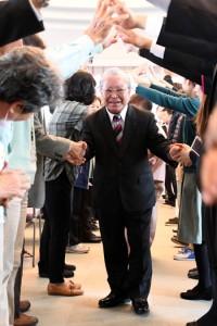 退任セレモニーで、職員らと握手しながらアーチをくぐる天城町の大久町長=26日、町役場